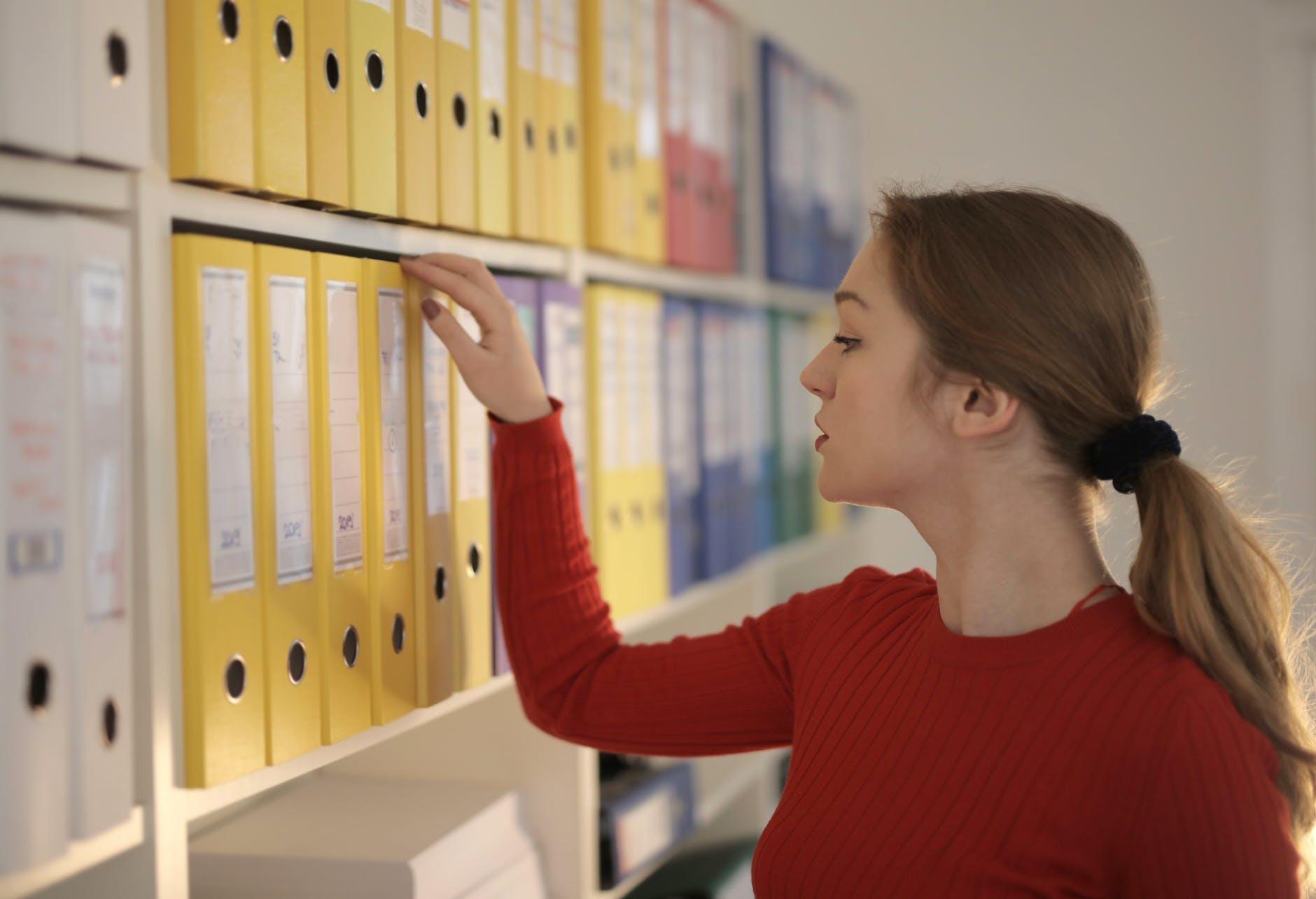 pondering female secretary picking folder in workplace